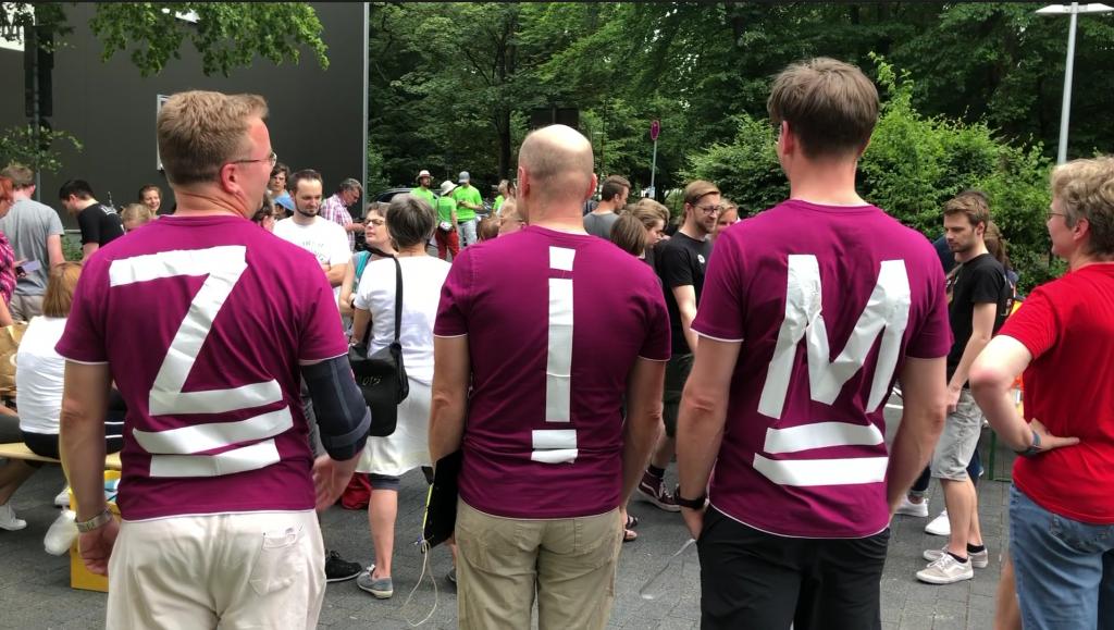 3 Personen von hinten fotografiert - auf den Rücken Buchstaben aufgeklebt